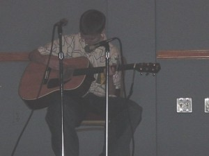 John singing and strumming his cute little ass off